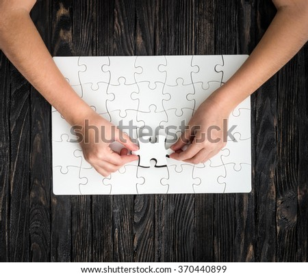 hands completing wthite puzzle with the last piece - stock photo