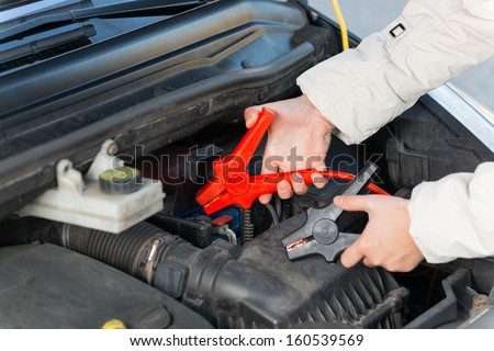 Hands connecting booster cables to a car battery - stock photo