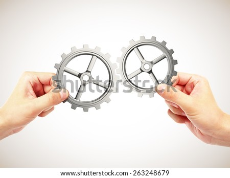 hands connecting gears on a gray background - stock photo