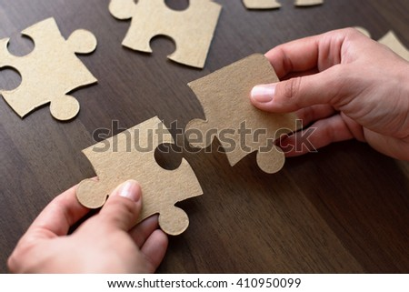 Hands connecting jigsaw puzzle. Education and learning concept. - stock photo