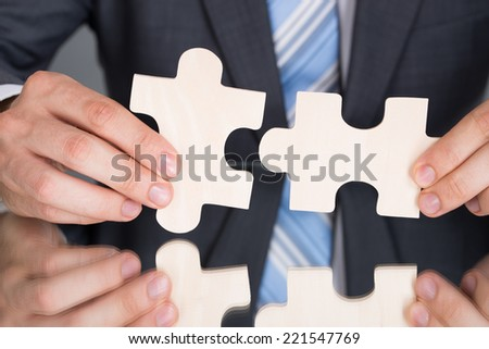 Hands connecting puzzle pices at the table