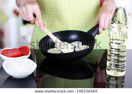 Hands cooking marrows in pan in kitchen - stock photo