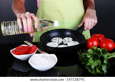 Hands cooking marrows in pan on gray background - stock photo