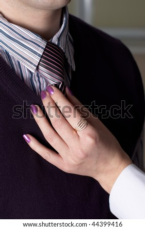 Hands correct a tie on the man in office