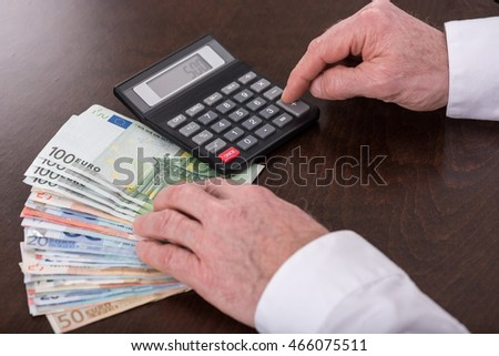 Hands counting money with calculator