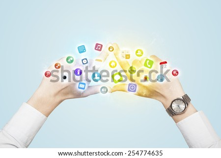 Hands creating a form with colorful mobile app icons in the center  - stock photo