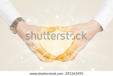 Hands creating a form with yellow shines in the center - stock photo