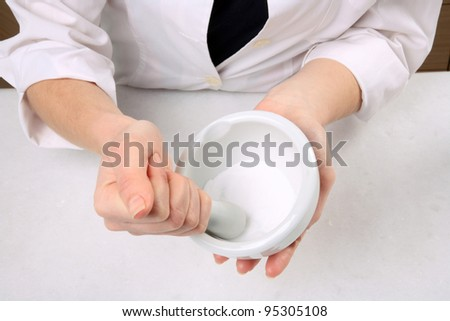 hands crushing on mortar with pestle - stock photo