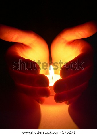 Hands cupped around a candle - stock photo