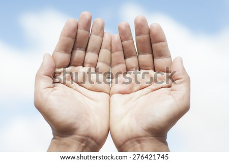 Hands cupped together on blue sky background - stock photo