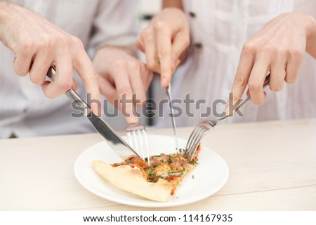 Hands  cutting  a slice of a pizza in cafe - stock photo