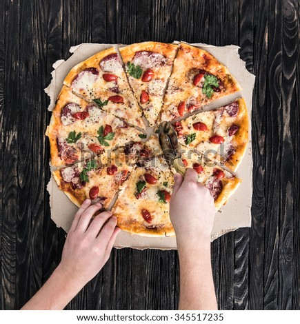 hands cutting pizza top view on dark wooden background - stock photo