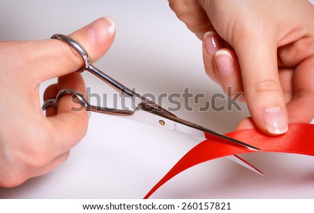 Hands cutting red ribbon
