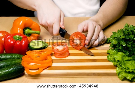hands cutting vegetables on a wood board