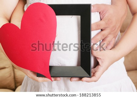 hands embracing a pregnant woman belly with her hands holding a wooden frame and a heart - stock photo