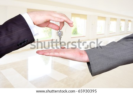 Hands exchanging the key to success, selling and buying an estate, white big modern building indoor in background, business and home concept - stock photo