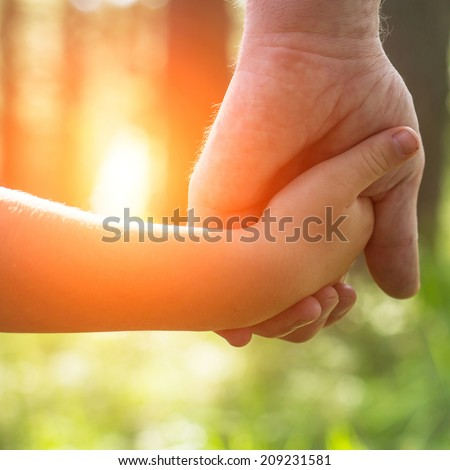 Hands, father with his son close-up, outdoors. - stock photo