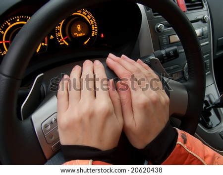 Hands female on a car wheel
