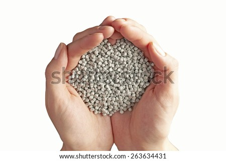 Hands filled with chemical granules isolated on white. Clipping path included