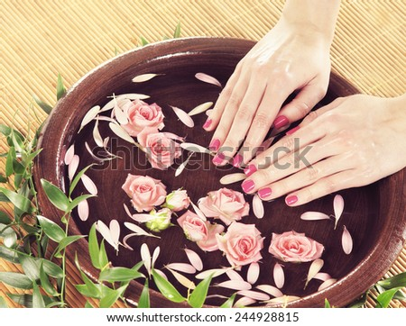 Hands, flowers, petals and ceramic bowl. Spa, recreation, manicure and skin care concept.  - stock photo