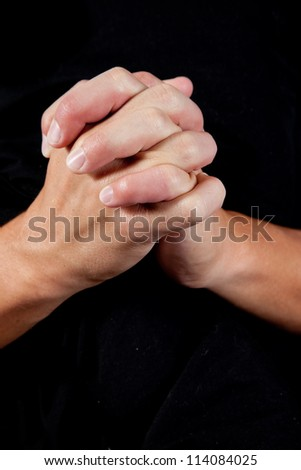 Hands folded as if in prayer or showing closeness and connection as in teamwork - stock photo