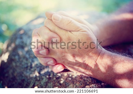 Hands folded in prayer. Instagram effect. Focus on thumbs. - stock photo