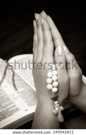 Hands folded in prayer on a Holy Bible. Black and white - stock photo