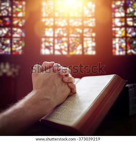 Hands folded in prayer on a Holy Bible in church concept for faith, spirituality and religion - stock photo
