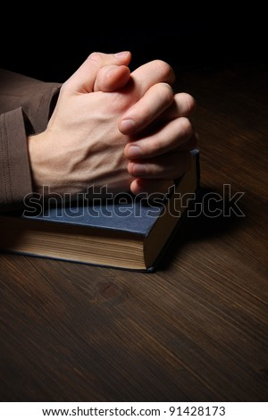 Hands folded in prayer over a Holy Bible - stock photo