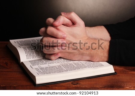 Hands folded in prayer over a Holy bible on wooden table on grey background - stock photo