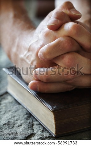 Hands folded in prayer over a Holy Bible resting on a stone baptismal font