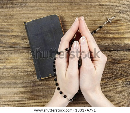 Hands folded in prayer over old Holy Bible. Wooden background. - stock photo