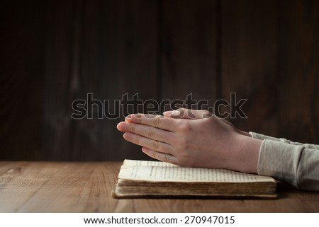Hands folded in prayer over open russian Holy Bible