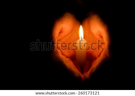 Hands folded in the shape of heart holding a burning candle on dark background with place for your text - stock photo