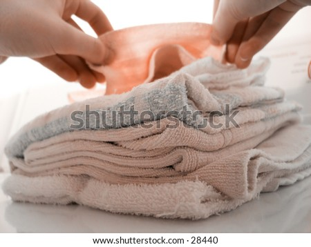 Hands folding laundry, atop a pile of folded towels. Focus on pile of towels. High key. - stock photo