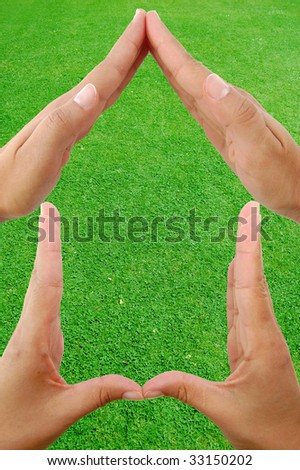 Hands form the shape of a house against a grass background