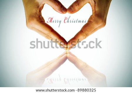 hands forming a heart and the sentence merry christmas - stock photo