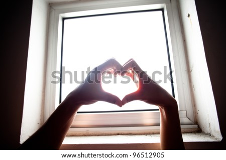 hands forming a heart on window light - stock photo
