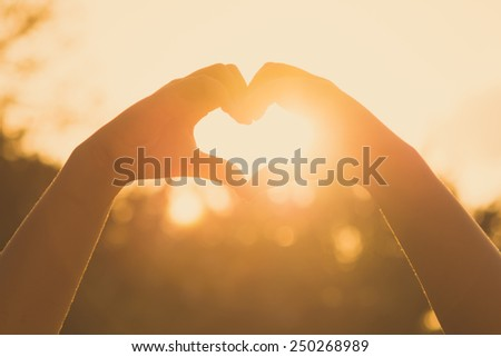 hands forming a heart shape at sunset - stock photo