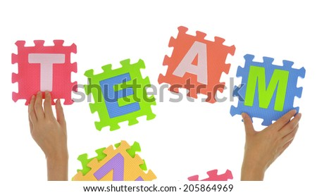 "Hands forming word ""Team"" with jigsaw puzzle pieces isolated"