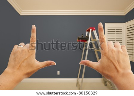 Hands Framing Grey Painted Room Wall Interior with Ladder, Paint Bucket and Rollers. - stock photo
