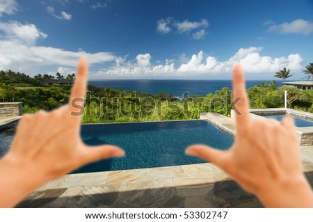 Hands Framing Pool and Hot Tub Overlooking the Ocean - stock photo
