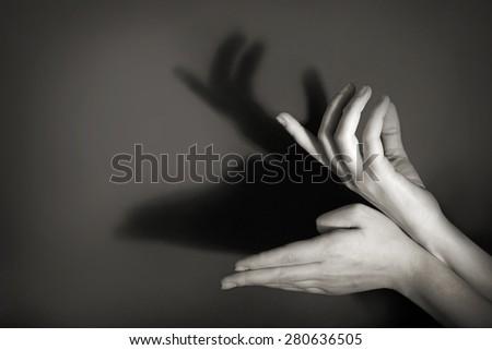 Hands gesture like deer on gray background - stock photo