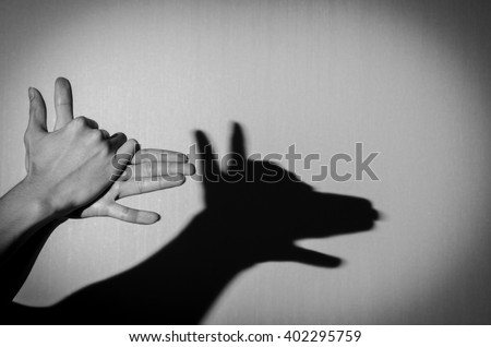 Hands gesture like dog face on gray background. - stock photo