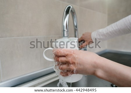 Hands girls gaining clean water in a cup of tap water in a sink in a white kitchen in the morning