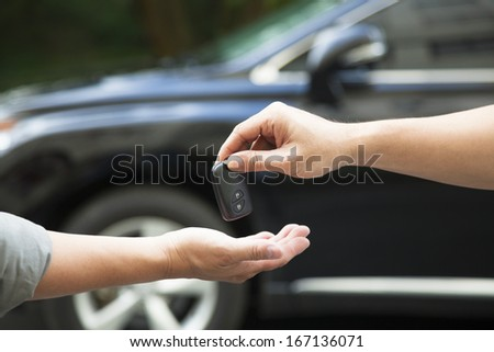 hands giving and receiving car key - stock photo