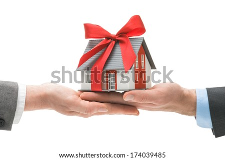 Hands giving house model to other hands. Concept of real estate and deal - stock photo
