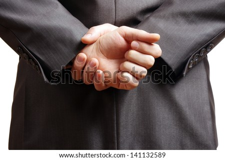 hands held behind the back of a suited man - stock photo
