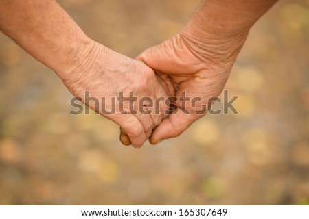 Hands held together on a natural yellow background - stock photo