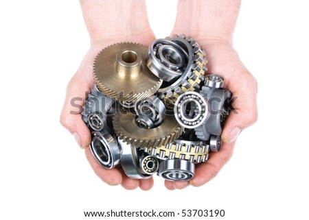 Hands hold a heap of bearings and a gears wheel on a white background